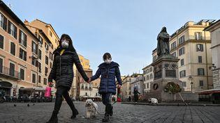 Une femme et une fille promènent leur chien sur une place déserte du Campo Dei Fiori dans le centre-ville de Rom (Italie), le 10 mars 2020. (ALBERTO PIZZOLI / AFP)