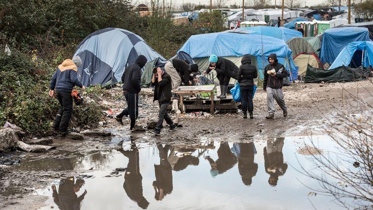 """Des migrants marchent dans la boue au milieu de la """"jungle"""" de Calais (Pas-de-Calais), le 20 novembre 2015. (PHILIPPE HUGUEN / AFP)"""