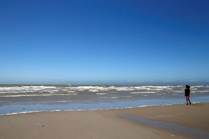 Béatrice Huret marche sur la plage de Dannes (Pas-de-Calais), le 15 juin 2017, un an après le départ detrois migrants iraniens depuis cette même plage. (PASCAL ROSSIGNOL / REUTERS)
