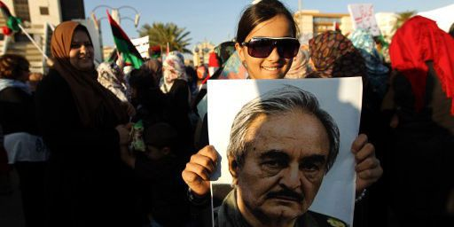 Une jeune Libyenne tient devant elle un portrait du général à la retraite Khalifa Haftar, lors d'un rassemblement en sa faveur fin mai 2014 à Benghazi, dans l'est de la Libye. (AFP PHOTO / ABDULLAH DOMA)