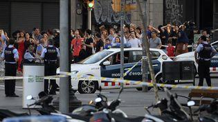 Des passants assistent à l'intervention de la police, le17 août 2017peu après l'attaque jihadiste survenuesur les Ramblas de Barcelone (Espagne). (JOSEP LAGO / AFP)