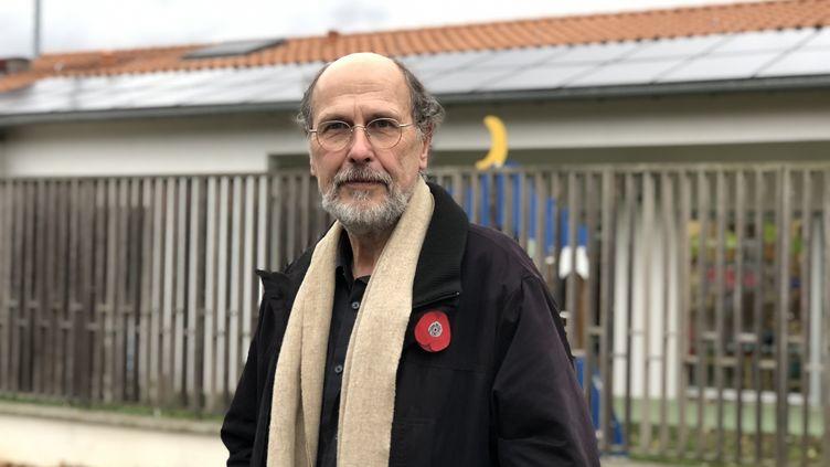 Gérard Bolet, vice-président de la communauté de communes Sicoval, pose devant des panneaux photovolatïques installés sur un bâtiment public. (MATTHIEU MONDOLONI / RADIO FRANCE)