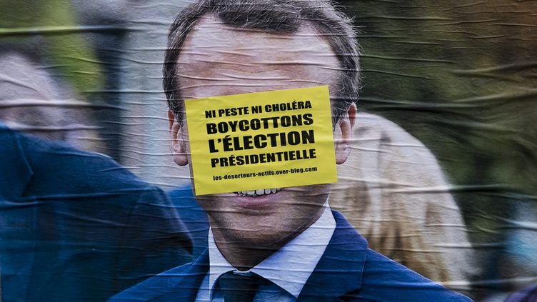 Un message appelant au boycott de l'élection présidentielle recouvre le visage d'Emmanuel Macron sur une affiche de campagne, à Paris, le 23 mars 2017. (MAXPPP)