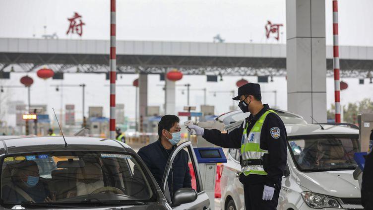 Un policier prend la température d'un automobiliste, le 24 janvier 2020 à Wuhan (Chine). (AFP)