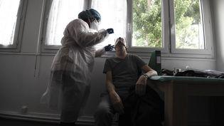 Un test virologique est effectué sur un homme , le 13 mai 2020 à Gennevilliers (Hauts-de-Seine). (ALAIN JOCARD / AFP)