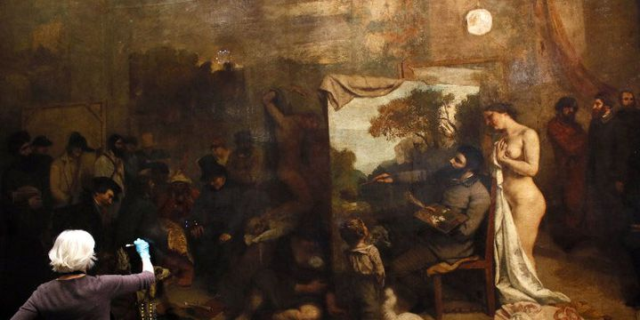 """Une restauratrice intervient sur la toile de Courbet """"L'Atelier du peintre"""" en décembre 2014 au musée d'Orsay  (PATRICK KOVARIK / AFP)"""