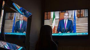 Une femme écoute le discours duPremier ministre Micheal Martin, à Dublin, en Irlande, le 30 décembre 2020. (ARTUR WIDAK / NURPHOTO / AFP)