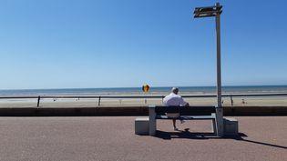 Un homme assis sur un banc face à la plage du Touquet, le 3 juillet 2019 (photo d'illustration) (RÉMI BRANCATO / FRANCE-INTER)