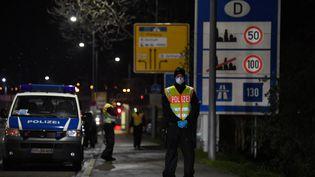 Un policier allemand portant un masque contre le coronavirus Covid-19 contrôle les véhicules à la frontière franco-allemande, entre Strasbourg et Kehl (Bas-Rhin), le 12 mars 2020. (PATRICK HERTZOG / AFP)