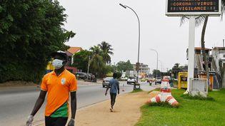 Passant dans une rue résidentielle d'Abidjan, en Côte d'Ivoire, le 24 mars 2020. (ISSOUF SANOGO / AFP)