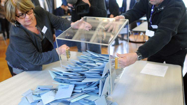 Des membres d'un bureau de vote vident une urne, le 30 mars 2014, à Angers (Maine-et-Loire). (JEAN-FRANCOIS MONIER / AFP)