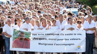 Des habitants de Marignane (Bouches-du-Rhône) participent à unemarche blanche, le 26 août 2013, à la mémoire de Jacques Blondel, tué alors qu'il tentait de stopper deux braqueurs. (BORIS HORVAT / AFP)