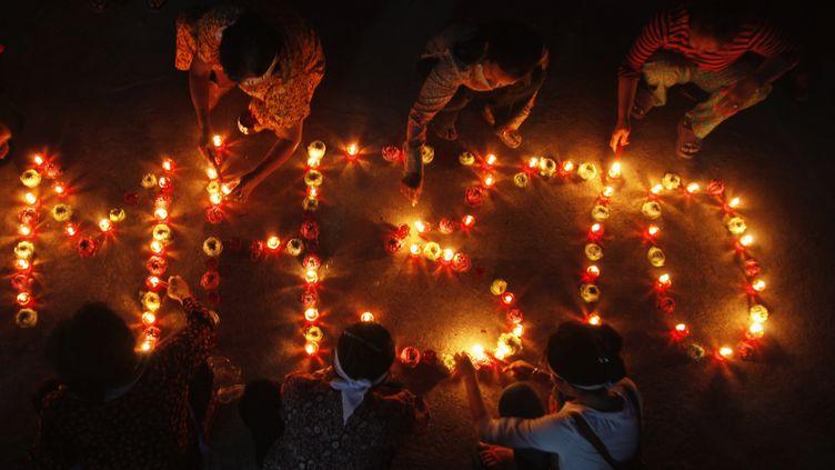 Le nom du vol MH370 dessiné avec des bougies, lors d'une cérémoniebouddhiste àPhnom Penh (Cambodge), le 17 mars 2014. (PRING SAMRANG / REUTERS )