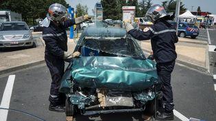 """Des sapeurs-pompiers présentent aux automobilistes une reconstitution d'accident, le 29 juin 2012, sur l'aire de Mâcon-Saint-Albain (Saône-et-Loire) sur l'autoroute A6, à l'occasion de l'opération de sécurite routière, """"Civil'été"""", organisée sur les routes de l'est de la France. (JEAN-PHILIPPE KSIAZEK / AFP)"""