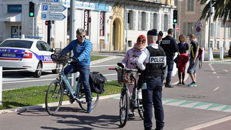 Un officier de police contrôle des passants pendant la période de confinement à Nice, le 18 mars 2020. (ARI? BOTBOL / HANS LUCAS)