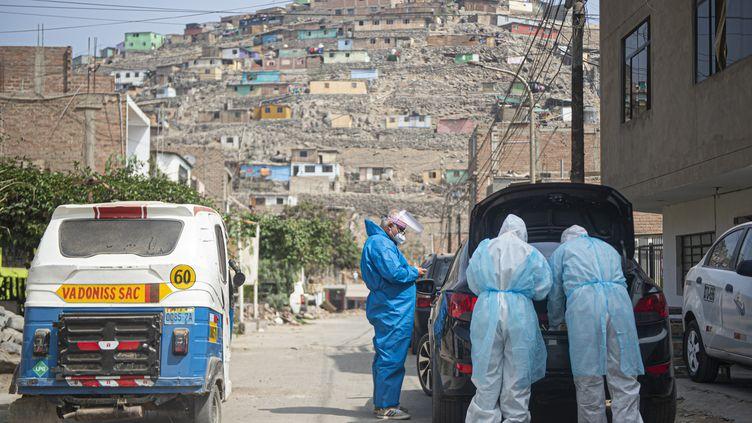 Des médecins rendent visite, le 11 juin 2020, à un malade du Covid-19 dans une banlieue de Lima, au Pérou, désormais un des 10 paysau monde comptant le plus de cas confirmés du virus. (ERNESTO BENAVIDES / AFP)
