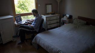 Un homme en plein télétravail dans sa chambre. Photo d'illustration. (LOIC VENANCE / AFP)