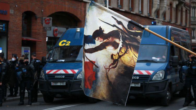 Drapeau à l'effigie de la Révolution françaiseet gendarmes mobiles, lors de la manifestation contre la précaritéet la réforme de l'assurance chômagedu samedi 5 décembre2020 à Toulouse. (SANDRA FASTRE / HANS LUCAS / AFP)