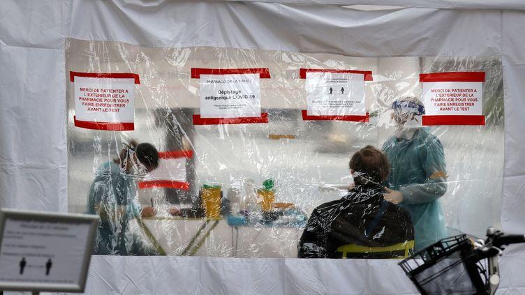 Des professionnels de santé effectuent des tests antigéniques rapides dans une rue de Paris, le 23 novembre 2020. (THOMAS COEX / AFP)