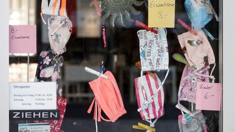 Des masques en tissu pour adultes et enfants dans une vitrine d'un magasin de Hambourg (Allemagne), le 21 avril 2020. (BODO MARKS / DPA / AFP)