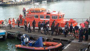 Des migrants venus pour la plupart d'Irak, d'Iran et d'Afghanistan débarquent d'un bateau de sauvetage de la SNSM après avoir été securus dans la Manche, le 15 septembre 2021, à Calais (Pas-de-Calais). (BERNARD BARRON / AFP)