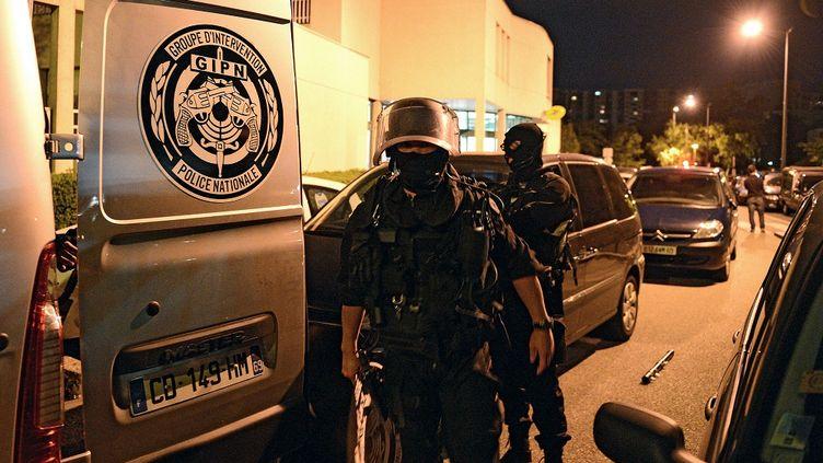 Les policiers avant une intervention dans l'appartement d'un suspect dans l'affaire du double meurtre, le 2 octobre 2012 à Echirolles (Isère). (PHILIPPE DESMAZES / AFP)