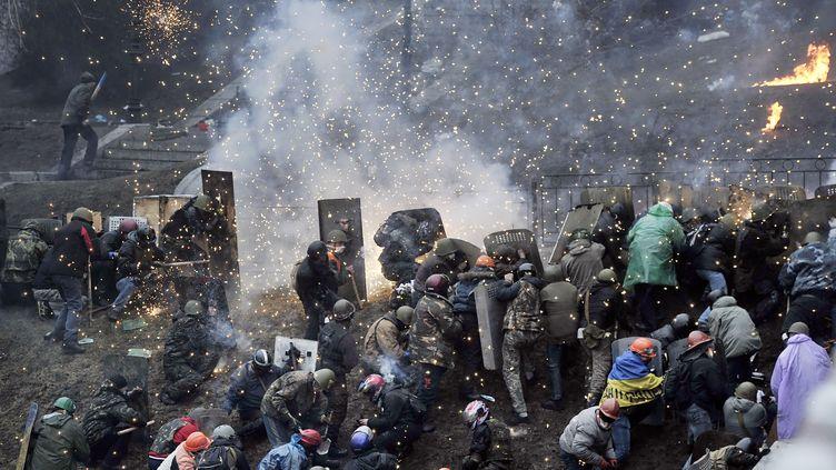 Des manifestants résistent à la police le 20 février 2014 à Kiev (Ukraine). (LOUISA GOULIAMAKI / AFP)