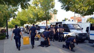Des policiers s'équipent au lendemain d'importantes violences à Trappes (Yvelines), le 20 juillet 2013. (MIGUEL MEDINA / AFP)