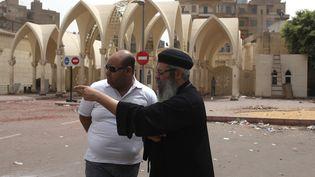 Un prêtre copte estime les dégâts après des heurts avec des musulmans, près de la principale cathédrale du Caire (Egypte), le 8 avril 2013. (ASMAA WAGUIH / REUTERS / AFP)