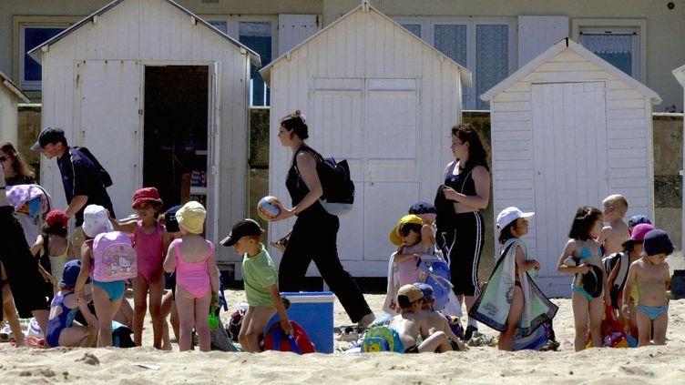Des enfants d'une colonie de vacances, le 9 juillet 2003 sur la plage de Courseulles, dans le Calvados. (MYCHELE DANIAU / AFP)