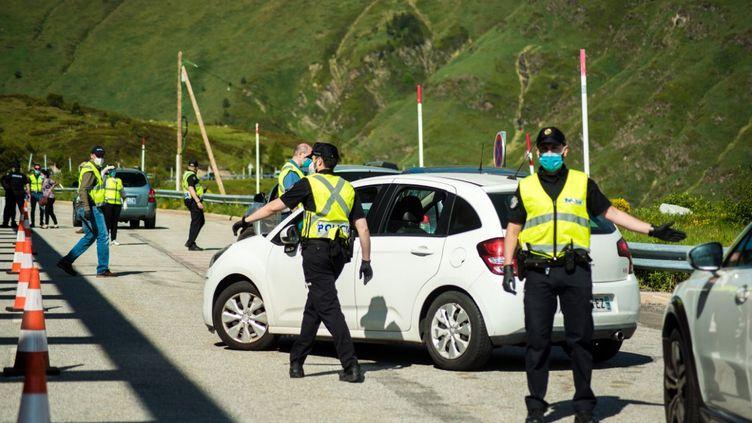 Des policiers contrôlentun véhicule arrivant de France à la frontière avec Andorre, le jour de sa réouverture, le 1er juin 2020. (STEPHANE FERRER YULIANTI / HANS LUCAS / AFP)