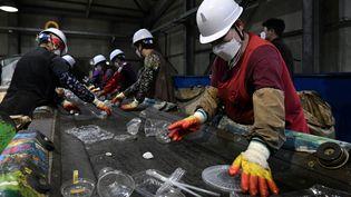 Des ouvrierstrient des bouteilles en plastique dans un centre de recyclage des déchets à Hoengseong, le 27 mai 2021. (JUNG YEON-JE / AFP)