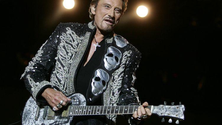 Sous des têtes de mort argentées, Johnny Hallyday chante au festival de poupet, à La Verrie (Vendée), le 22 juillet 2006. (MAXPPP)