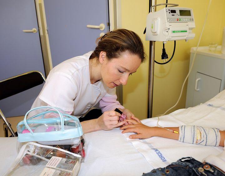 Une socio-esthéticienne vernit les ongles d'une patiente au CHU de Bordeaux, le 4 novembre 2008. (JEAN-PIERRE MULLER / AFP)