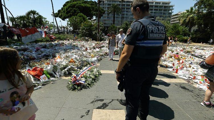 Un policier municipal se recueille sur la promenade des Anglais à Nice (Alpes-Maritimes), le 25 juillet 2016. (CITIZENSIDE/ROLAND MACRI / CITIZENSIDE / AFP)