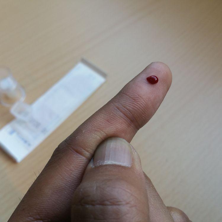 Une goutte de sang se forme à l'extrémité de mon doigt, après que je me suis piqué avec l'autopiqueur fourni dans le kit d'autotest de dépistage du VIH. (THOMAS BAIETTO / FRANCETV INFO)
