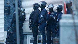 Des policiers en attente à Forest, une commune de Bruxelles (Belgique), le 15 mars 2016; lors d'une vaste opération anti-terroriste. (LAURENT DUBRULE / EPA / AFP)