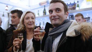 Marine Le Pen et Florian Philippot boivent un verre de champagne sur le marché de Noël des Champs Elysées, à Paris, le 22 décembre 2014. (KENZO TRIBOUILLARD / AFP)