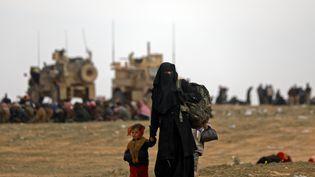 Une femme et son enfantdans le village de Baghouz (Syrie), dernier bastion revendiqué par le groupe Etat islamique. (DELIL SOULEIMAN / AFP)