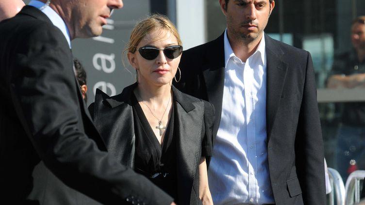 Madonna arrive à Marseille avec ses gardes du corps pour rencontrer les ouvriers blessés dans l'effondrement du toit de la scène où elle devait chanter, au stade Vélodrome (19 juillet 2009) (TSCHAEN/SIPA)