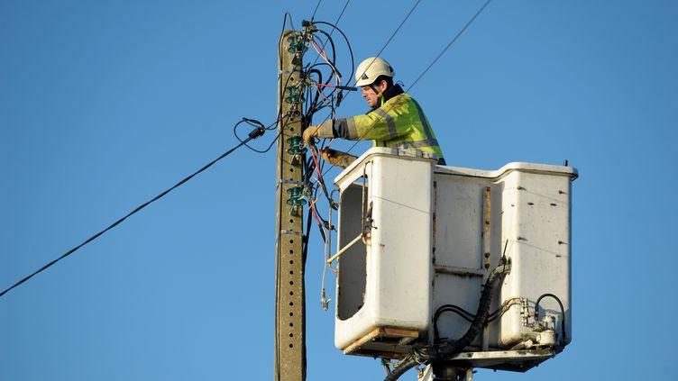 Un technicien tente de rétablir l'électricité à Tregunc, dans le Finistère, le vendredi 13 janvier. (Illustration / FRED TANNEAU / AFP)