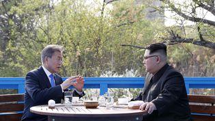 Le leader nord-coréen Kim Jong-un et le président sud-coréen Moon Jae-in discutent sur un pont près de la ligne de démarcation entre les deux pays, dans le village de Panmunjom, le 27 avril 2018 (KOREA SUMMIT PRESS POOL / KOREA SUMMIT PRESS POOL)