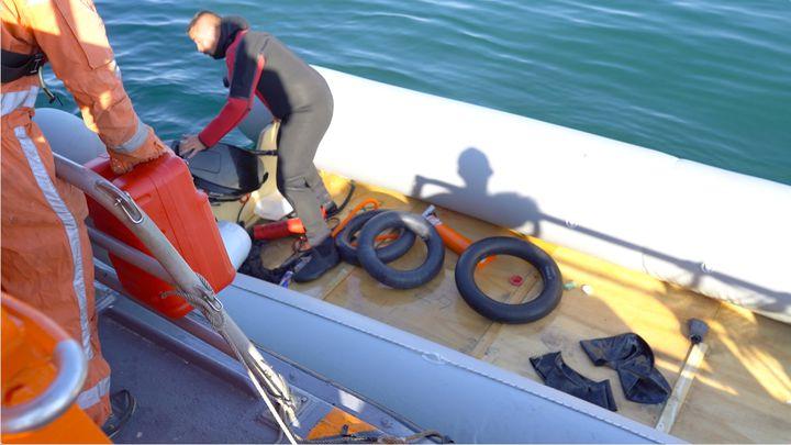 Les sauveteurs de la SNSM vident l'embarcation en détresse avant de la remorquer. (PIERRE-LOUIS CARON / FRANCEINFO)