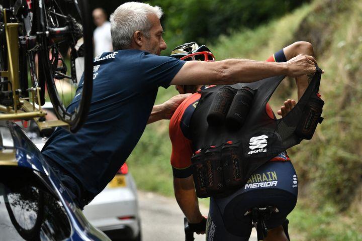 Lors du Tour de France de 2018, le 21 juillet, l'italien Sonny Colbrelli se charge en bouteilles d'eau, lors de la 14e étape entre Saint-Paul-Trois-Châteaux et Mende. (MARCO BERTORELLO / AFP)