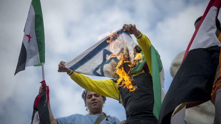 Des manifestants pro-palestiniens brûlent un drapeau israélien place de la République, à Paris, le 26 juillet 2014. (ZACHARIE SCHEURER / AFP)