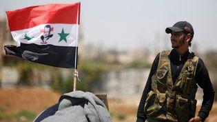 Un soldat de l'armée syrienne à côté d'un drapeau syrien portant l'effigie de Bachar Al-Assad, le 10 juillet 2018, à Deraa en Syrie. (Photo d'illustration) (OMAR SANADIKI / REUTERS)