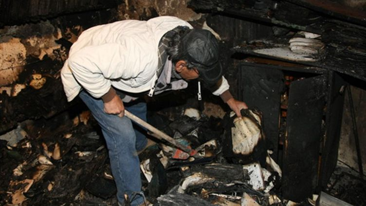 Un homme fouille les débris après l'incendie de la synagogue de La Canée en Crète (Grèce) (AFP/Costas Metaxakis)