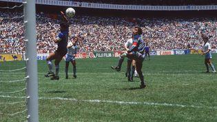 """Diego Maradona inscrit un but contesté """"un peu de la tête"""", """"un peu de la main de Dieu"""" contre l'Angleterre en 1986, lors de la Coupe du monde auMexique. (SVEN SIMON / DPA / AFP)"""