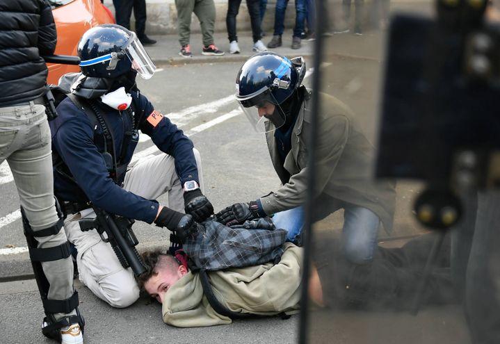 Deux policiers fouillent le sac à dos du manifestant, le 23 mars 2019 au Mans. Le LBD de l'un d'eux pend en bandoulière et touche le crâne de l'homme à terre. (MAXPPP)