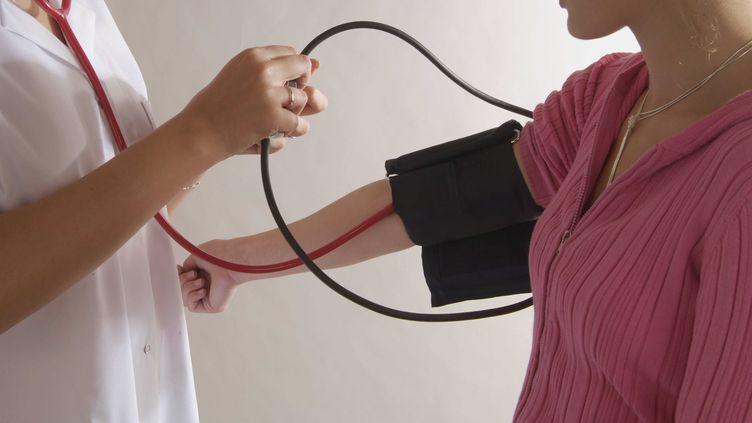 Un médecin prend la tension d'une patiente, le 29 mars 2007. (HOUIN GERARD / SIPA)